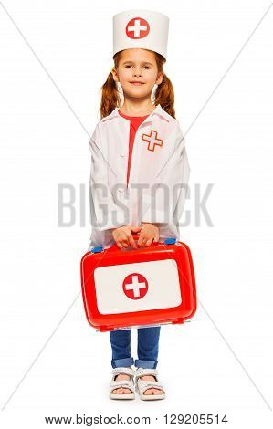 Beautiful little girl with pigtails dressed like a doctor holding red toy first-aid kit isolated on white