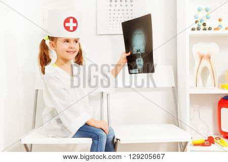 Beautiful girl with pigtails uniformed as doctor exploring skull radiography at the medical room.