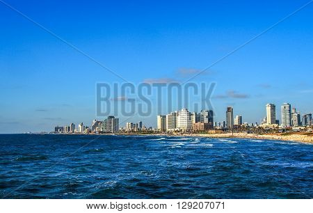 TEL-AVIV ISRAEL - MAY 8: View of the waterfront the beach and the hotels on the Mediterranean coast from the port of Old Jaffa sunset light in Tel Aviv Israel on May 8 2016