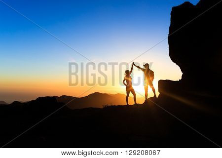 Teamwork couple helping hand trust help silhouette success in mountains. Team of climbers man and woman. Hikers celebrate with hands up help each other on top of mountain climbing together beautiful sunset landscape.
