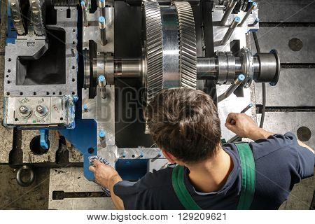 Working man clean parts a small steam turbine. Metal gears. Gear wheels of the engine.