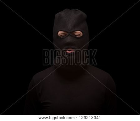 Masked thief over black background. Dangerous man in black balaclava ready for robbery or burglary. Mafia concept.