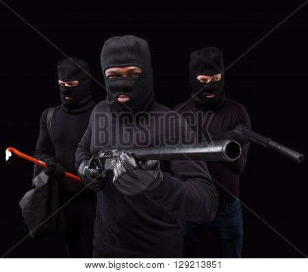 Portrait of dangerous robbers or burglaries with rifles  and crowbars over black background in studio. Studio shot. Isolated on black.