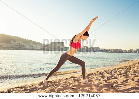 Young slim fit woman doing exercises on open air