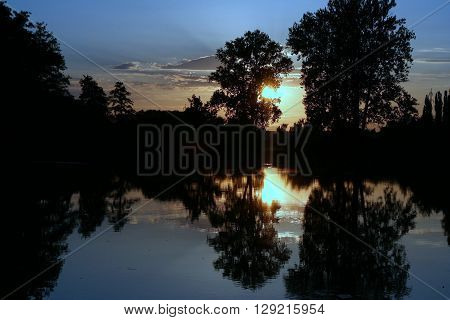 Water reflection in the bayou on dead arm of the river Elbe in Czech republic. Blue and golden colors.