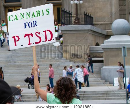 BOISE IDAHO/USA - MAY 7 2016: Woman displaying a sign in support for cannabis for PTSD patients for the Global Marijuana March in Boise Idaho
