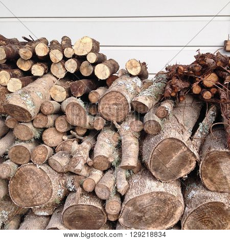 Firewood logs stacked in front of a weatherboard home, ready for winter