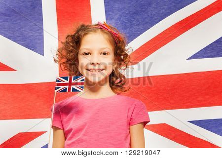 Funny curly-haired smiling girl with little pennon against British flag