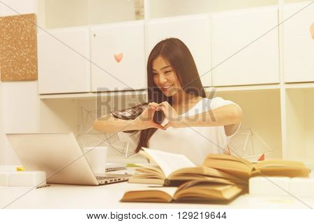 Toned image. Asian student communicating with friend abroad via Skype and showing heart while studying in library. Brunette lady smiling.