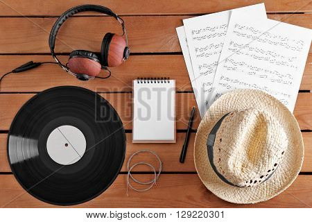 Headphones, music sheets and straw hat on wooden surface, top view