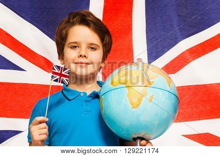 Proud English boy with little flag and globe at his hands standing in front of British flag