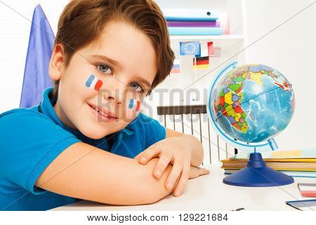 Smiling French boy learning geography with the globe sitting at the classroom