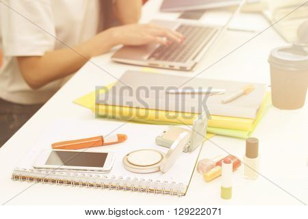 Closeup picture of cosmetics represented among exercise-books, documents and university, colleage or school things for studying. Toned image.