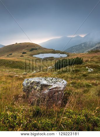 Foggy Mountain Landscape with a Tarn and a Rock in Foreground at Sunset