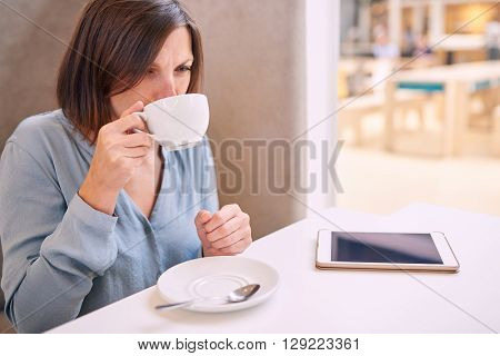 Beautiful mature caucasian woman taking a sip of her warm fresh cappaccino in a modern well lit coffee shop with her tablet lying on the table infront of her.