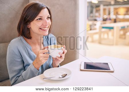 white woman with a beautiful smile busy smiling while looking off camera and holding a coffee as she looks off camera with her tablet lying on the table infront of her and excellent copy space.