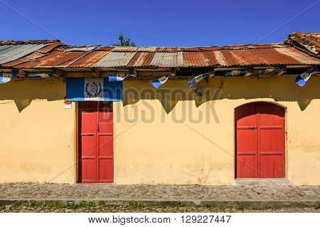 Antigua Guatemala - October 5 2014: Old painted house adorned with Guatemalan flags in colonial city & UNESCO World Heritage Site of Antigua.