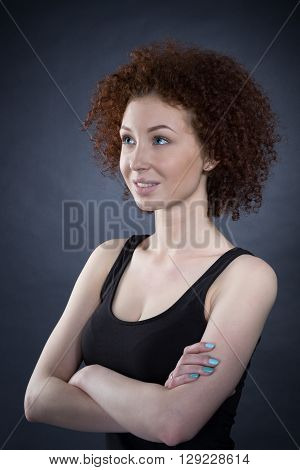 Girl With Arms Folded Standing Over Gray Background And Looking Away