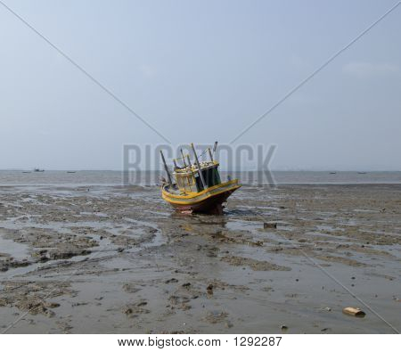 gray and yellow fishing boat stranded in the mud. chonburi province poster