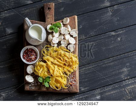 Raw ingredients for cooking pasta with mushroom cream sauce - pasta mushrooms cream spices. On rustic wooden board on dark background