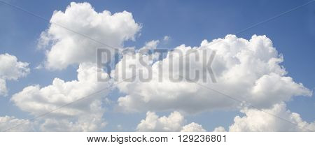 White fluffy clouds in deep blue summer sky. Spiritual calmness and serenity background