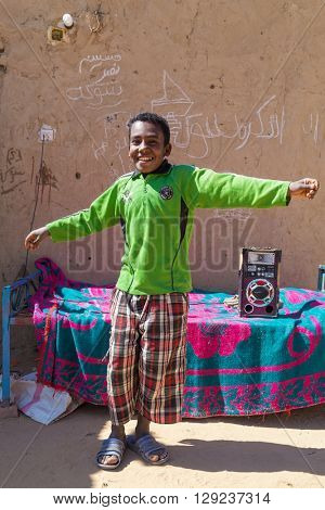 ASWAN, EGYPT - FEBRUARY 7, 2016: Happy local boy dancing on the street of Nubian village on the Nile.