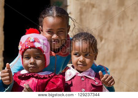 ASWAN, EGYPT - FEBRUARY 7, 2016: Local girls posing in front of the house in Nubian village on the Nile.
