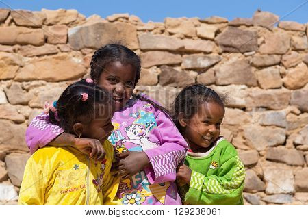 ASWAN, EGYPT - FEBRUARY 7, 2016: Local girls in Nubian village on the Nile posing for camera.