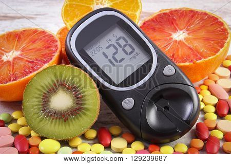 Glucometer with result of measurement sugar level fresh fruits and medical pills tablets and supplements concept of diabetes healthy lifestyle and nutrition