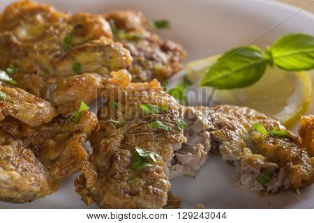 Fried pork brain with lemon and herbs on white plate