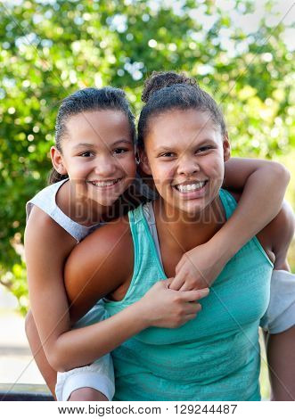 An older teenage girl carries a younger girl on her back both smiling.