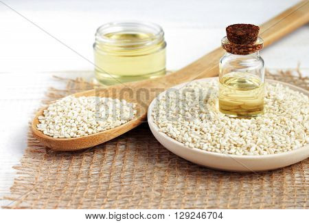 Sesame oil in bottles, sesame seeds scattered. Culinary and cosmetic use.
