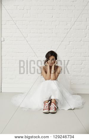 Young bride sitting on floor in red sneakers and wedding dress, looking at camera.