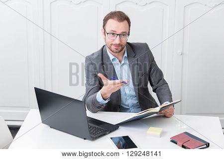 Businessman at the office desk gesticulates with a pen in his hand