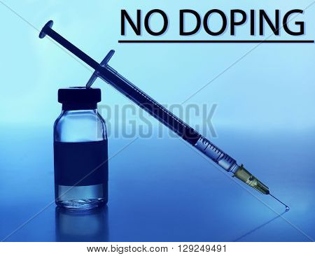 Stop doping concept. Ampule and syringe on blue background