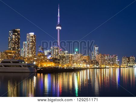 TORONTO CANADA - 16TH APRIL 2015: A view of Toronto downtown at dusk showing buildings condos the CN Tower and boats.