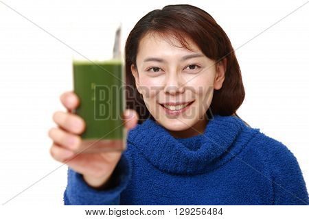 portrait of woman with green vegetable juice on white background