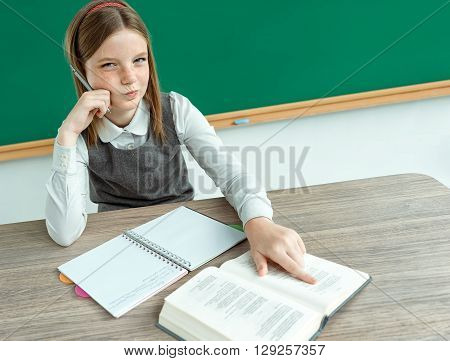 Skeptical young girl looking carefully suspicious skepticism on face. Photo of teen school girl creative concept with Back to school theme