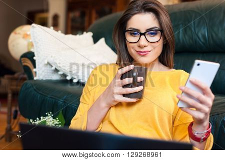 Woman sitting on the floor using a laptop and mobile phone holding a cup of coffee.