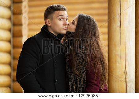 Happy young couple in love kissing on porch of cottage. Male and female fashion model outdoor