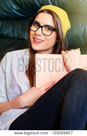Hipster woman sitting on the floor next to a couch, holding a book