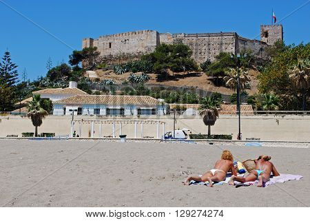 FUENGIROLA, SPAIN - JUNE 20, 2008 - Holidaymakers sunbathing on the beach with Sohail castle to the rear Fuengirola Malaga Province Andalucia Spain Western Europe, June 20, 2008.