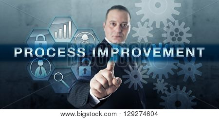Manager is touching PROCESS IMPROVEMENT on a virtual interactive display. Business metaphor for a systematic method aimed at process optimization and organizational development.