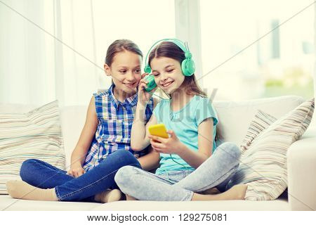 people, children, technology, friends and friendship concept - happy little girls with smartphone and earphones sitting on sofa and listening to music at home