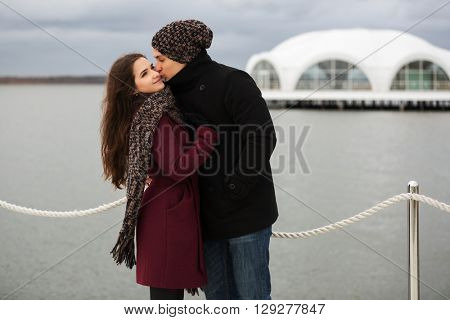Happy young couple in love. Male and female fashion model outdoor. Young man and woman kissing on pier