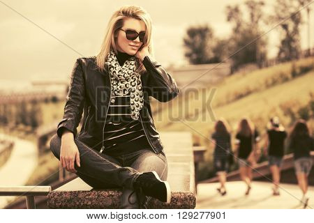 Happy young fashion woman in leather jacket on city street. Female fashion model in sunglasses outdoor