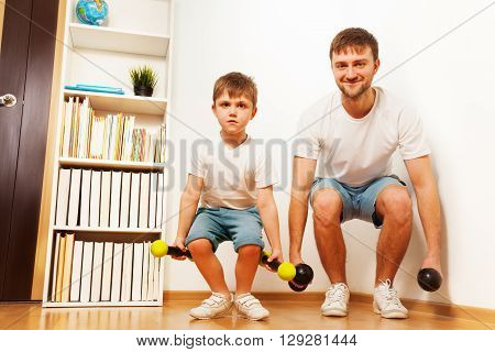 Father and kid son training at home, doing knee bending with dumbbells together