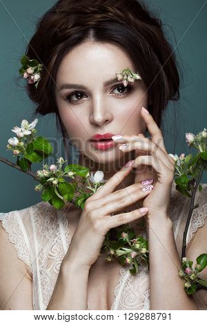 Beautiful brunette girl in lingerie with a gentle romantic make-up, pink lips, holding flowers. The beauty of the face. Portrait shot in the studio.