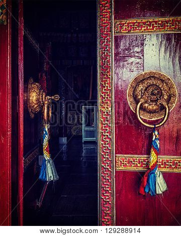 Vintage retro effect filtered hipster style image of open door of Spituk Gompa (Tibetan Buddhist monastery) with ornamented decorated door handle. Ladakh, India