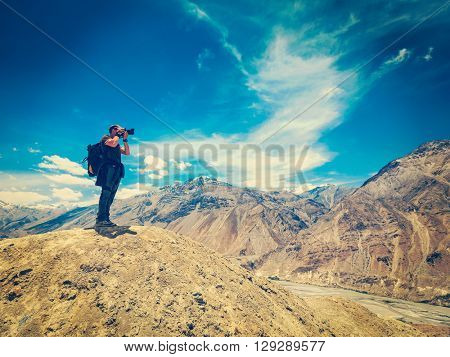 Vintage retro effect filtered hipster style image of photographer taking photos in Himalayas mountains. Spiti valley, Himachal Pradesh, India